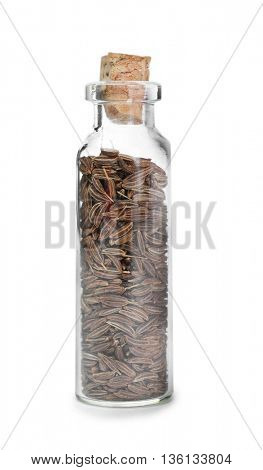 Cumin seeds in glass bottle on white background