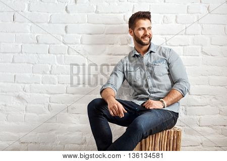 Happy young goodlooking caucasian man sitting at white brick wall, plenty of copyspace.