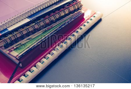 Notebook stack on blackboard background. Back to school concept with space for text. School supplies. Schoolchild and student studies accessories. Back to school concept. Toned image.