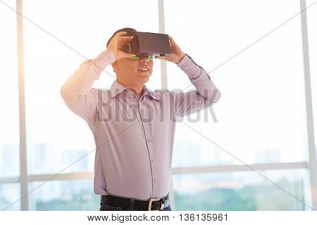 Businessman using virtual reality glasses in office