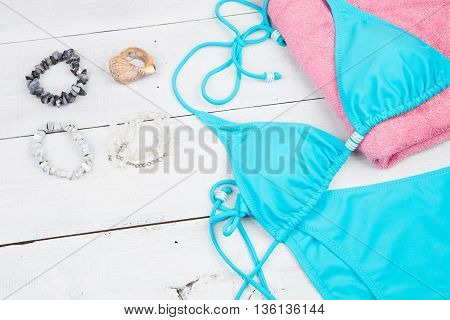Summer Women's Fashion With Blue Swimsuit, Pink Towel, Shell And Bijou On White Wooden Desk