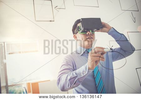 Business executive in VR headset drawing scheme on glass wall