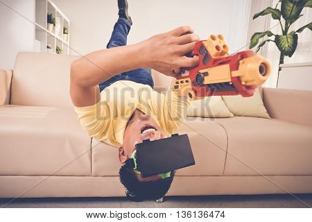 Adult man with gun and VR glasses playing at home