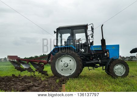 Tyumen, Russia - June 24, 2016: The 5th open championship of Russia on a plowed land. Young operator rises plow on border of field on Belarus tractor in rainy weather