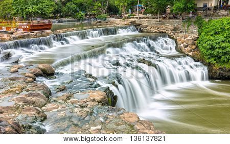 Dong Nai, Vietnam - June 19th, 2016: Falls in park destinations  summer morning with water flowing down smooth as silk sheet stone steps natural scenery beautiful attract tourists to relax on weekend in Dong Nai, Vietnam
