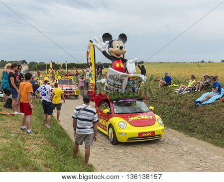 Quievy, France - July 07 2015: Mickey Mouse caravan during the passing of the Publicity Caravan on a cobblestoned road in the stage 4 of Le Tour de France on July 7 2015 in Quievy France.