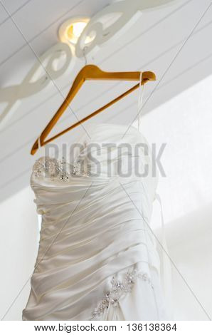 close up white wedding dress hanging on a coat hanger