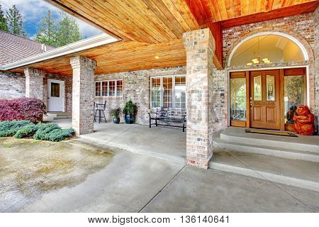 Cozy Entrance Porch Of A Large Brick House. Patio Area With Concrete Floor And Brick Columns.