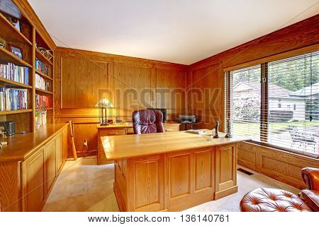Interior Of The Wooden Cabinet In The American Style With Desktop, Bookcase And Brown Leather Chair.