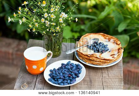 Bouquet of daisies, pancakes with berries and a glass of milk on a wooden table close-up view from above. Pancakes and milk for breakfast.