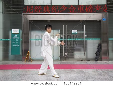 Shenzhen, China - Jun 13, 2016: Chinese master practice Tai Chi on the side walk of a street. It is an internal Chinese martial art practised for both its defense training and its health benefits.