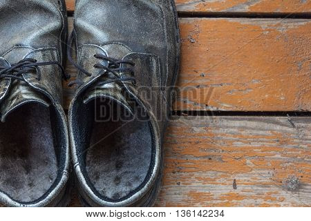 the old genuine leather shoes on a wooden background