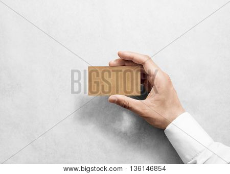 Hand hold blank plain craft business card design mockup. Brown calling card mock up template holding arm. Visit pasteboard kraft paper display front. Small offset texture card print. Logo branding