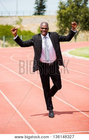 Excited businessman standing on the running track with hands raised