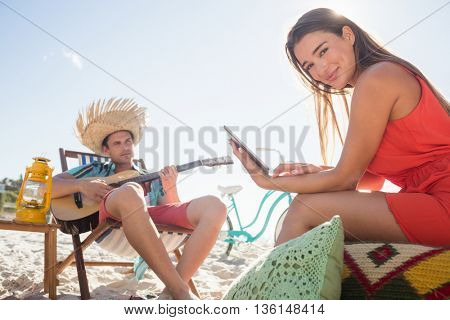 Friends lying and looking a tablet on the beach