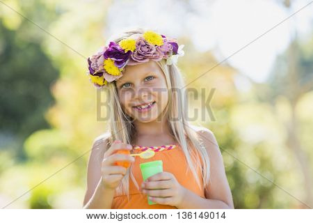 Portrait of cute young girl holding bubble wand in park