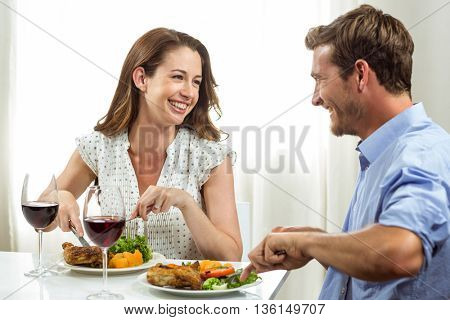 Happy couple laughing while having lunch at home