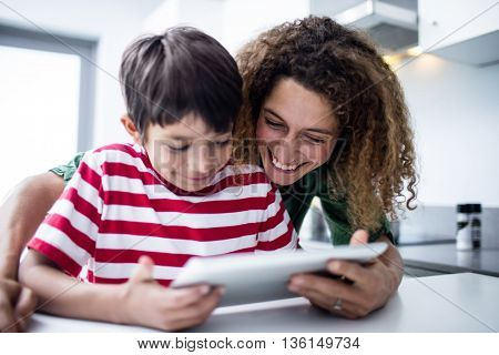 Mother and son using digital tablet in kitchen at home
