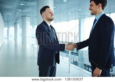 Happy businessmen shaking hands while standing in office corridor