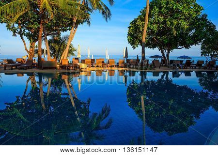 Sunset on the beach resort. An oceanfront pool surrounded by palm trees. Palm trees reflected in smooth water