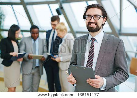 Businessman at meeting looking at camera and smiling