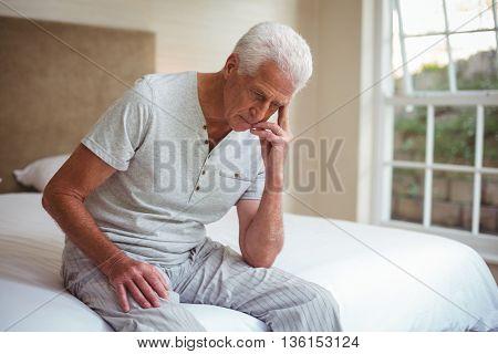 Worried senior man sitting on bed in room