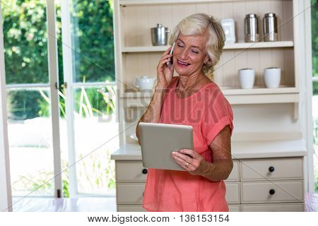 Senior woman holding digital tablet while talking on mobile phone at home