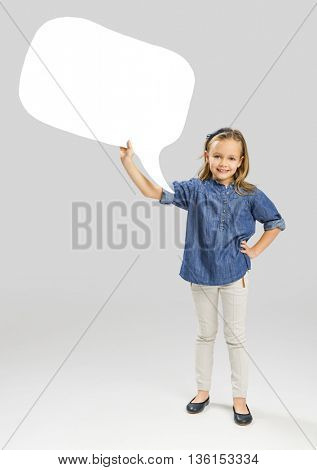 Beautiful little girl holding and showing a speech balloon
