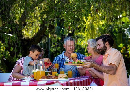 Happy family enjoying while having food at table in yard