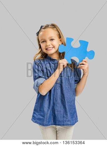 Beautiful little girl holding a blue Puzzle