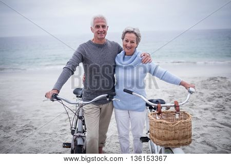 Portrait of happy senior couple with their bike on the beach