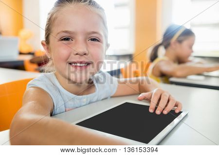 Cute girl posing at desk with tablet pc in classroom at elementary school
