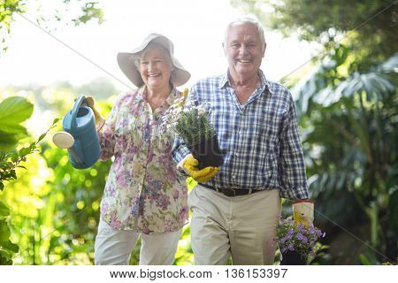 Portrait of cheerful senior man and woman gardening with equipment