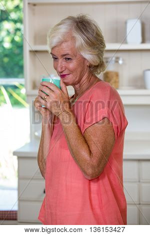 Thoughtful senior woman having coffee in kitchen at home
