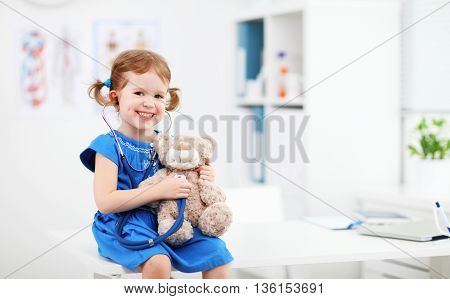 Child girl playing doctor with a teddy bear