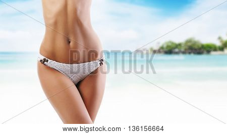 Close-up of beautiful female body. Sporty woman with a perfect body relaxing on beach at summer. Sea and sky background.