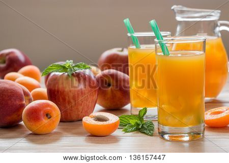 Apricot peach apple juice in glasses with ice near the jar of juice and scattered apricots peaches apple mint on a light wooden background. Apricot peach apple juice with ice. Horizontal. Daylight.