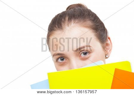 Smiling student girl looking trough colorful notebooks, isolated on white background