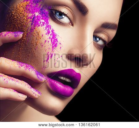 High fashion model girl portrait with colorful powder make up. Beauty woman with bright color makeup. Close-up of Vogue style lady face, Abstract colourful make-up, Art design. Black background