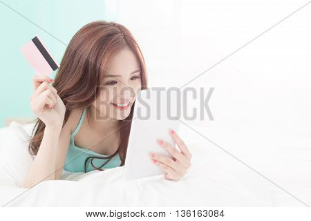 smile woman shopping on internet by digital tablet pc or smart phone and she lying on the bed at home asian girl