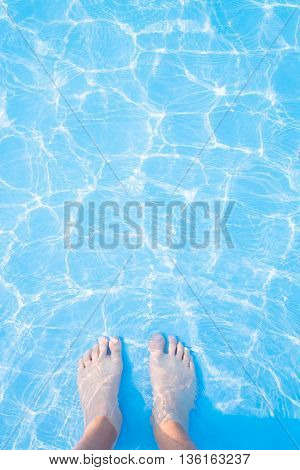 Barefoot and blue swimming pool rippled water background great for your background and texture