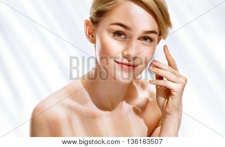 Young woman removing make up from her face with cotton pad. Photo girl on white background with palm leaf shadows. Youth and skin care concept