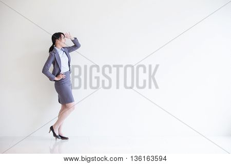 business woman stand and look something with white wall background great for your design or text asian