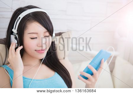 Young woman closed eye enjoying the music by smart phone and relax sit at home asian beauty