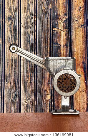 Old manual meat grinder on wooden timber wall background taken closeup.