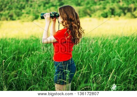 Girl In A Red  Looking Through Binoculars. Woman Looking Through