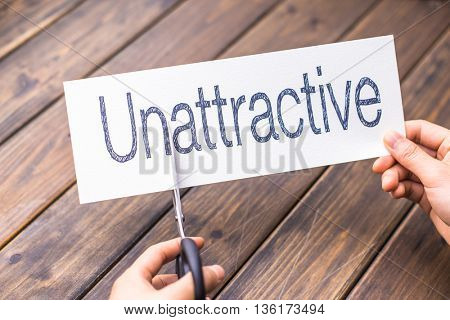 woman cuts white paper with word unattractive on table