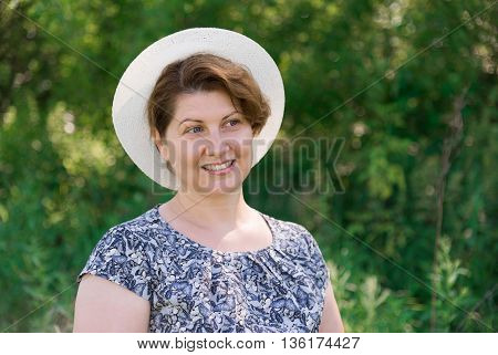 Woman in a summer hat on nature