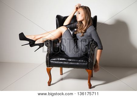 Portrait of young woman in dress and high heels on chair with eyes closed