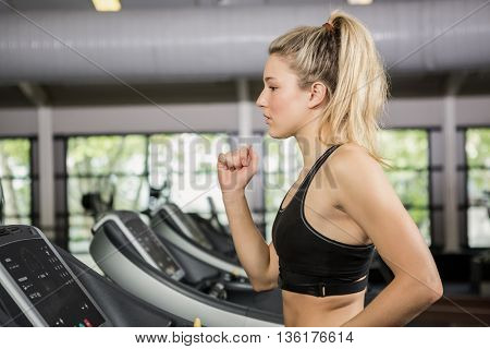 Woman walking on treadmill at gym